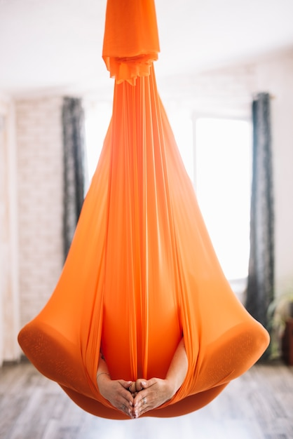 Mulher, prática, aero, ioga, em, laranja, hammock Foto gratuita