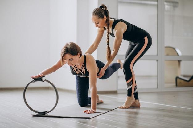 Mulher, prática, ioga, em, a, ginásio, com, a, instrutor Foto gratuita