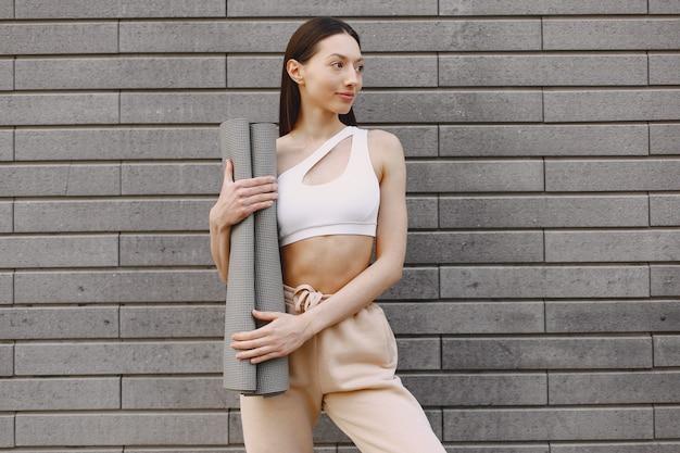Mulher praticando ioga avançada contra uma parede urbana escura Foto gratuita