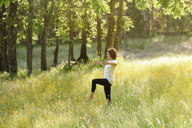 Mulher praticando ioga em um prado florido Foto Premium