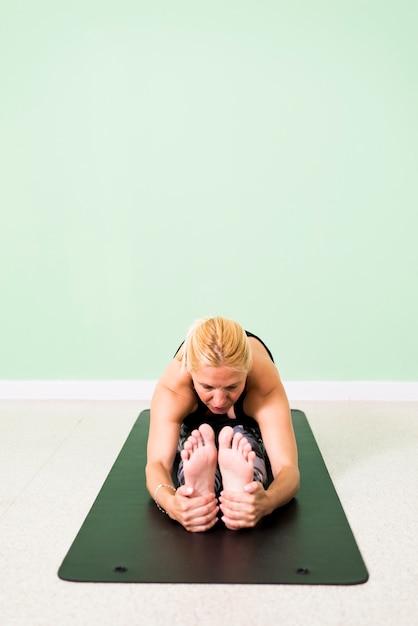 Mulher praticando ioga, sentado na posição de paschimottanasana (curvatura para a frente assentada) no chão Foto Premium