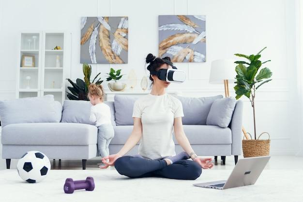 Mulher praticando ioga usando fone de ouvido com tecnologia vr na aula online em casa. Foto Premium
