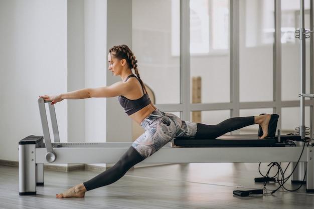 Mulher praticando pilates em um reformador de pilates Foto gratuita