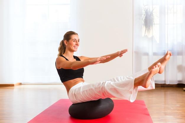 Mulher praticando poses na bola de exercício Foto Premium