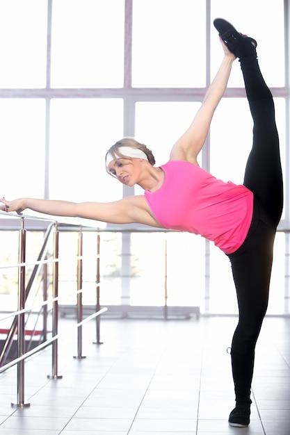Mulher praticando seus alongamentos de ioga no corrimão Foto gratuita