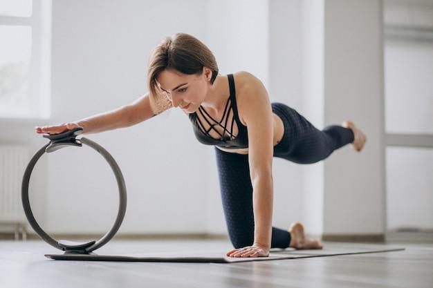 Mulher praticando yoga no ginásio em uma esteira Foto gratuita