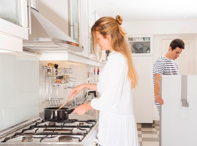 Mulher preparando comida enquanto o marido olhando na geladeira Foto gratuita