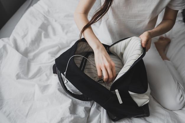 Mulher procurando algo em uma mochila Foto Premium
