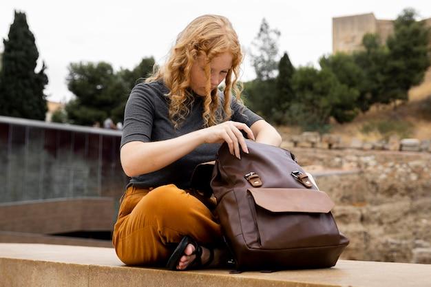 Mulher procurando na mochila Foto gratuita