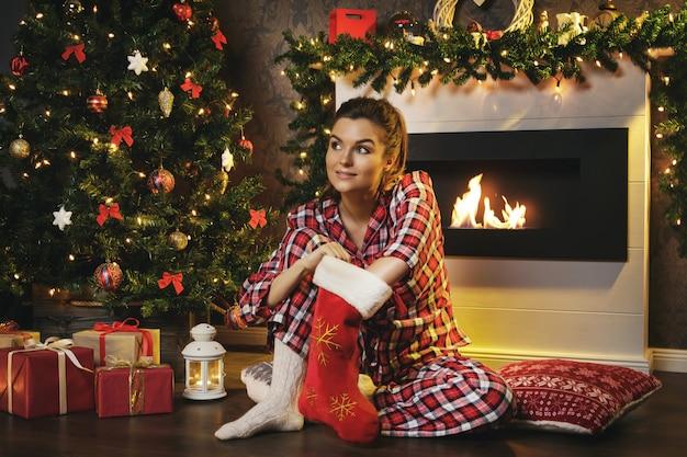 Mulher procurando presentes na meia de natal Foto Premium