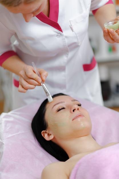 Mulher profissional que aplica o creme verde com uma escova Foto gratuita