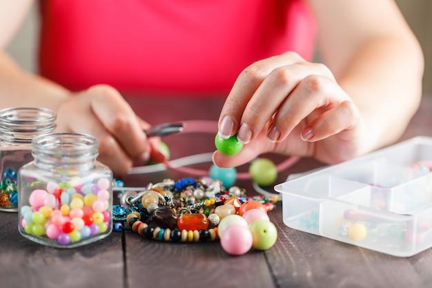 Mulher projetando colar colorido com miçangas plactic Foto Premium