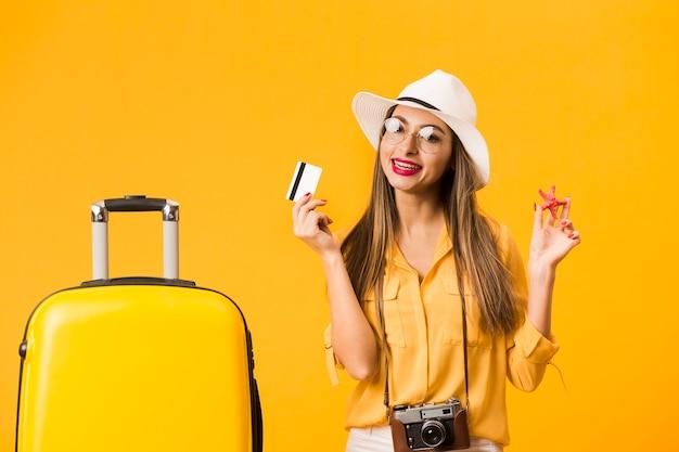 Mulher pronta para a viagem posando com cartão de crédito e bagagem Foto gratuita