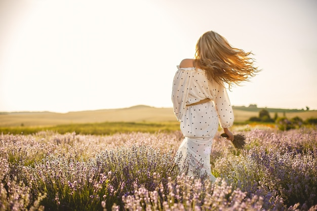 Mulher provençal relaxante no campo de lavanda. senhora de vestido branco. menina com bouquete de flores. Foto gratuita