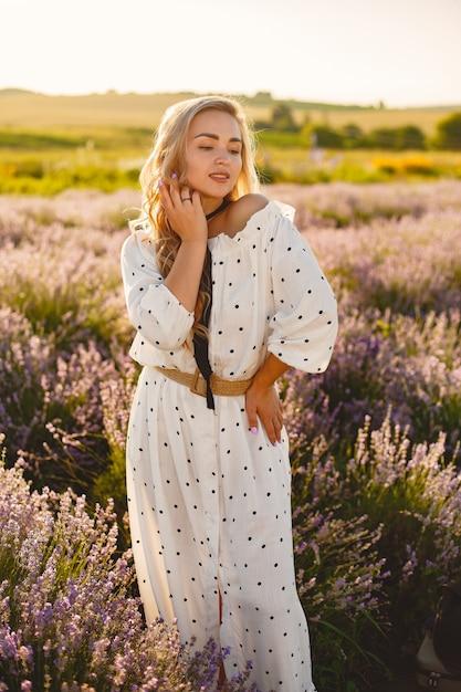Mulher provençal relaxante no campo de lavanda. senhora de vestido branco. menina com um chapéu de palha. Foto gratuita