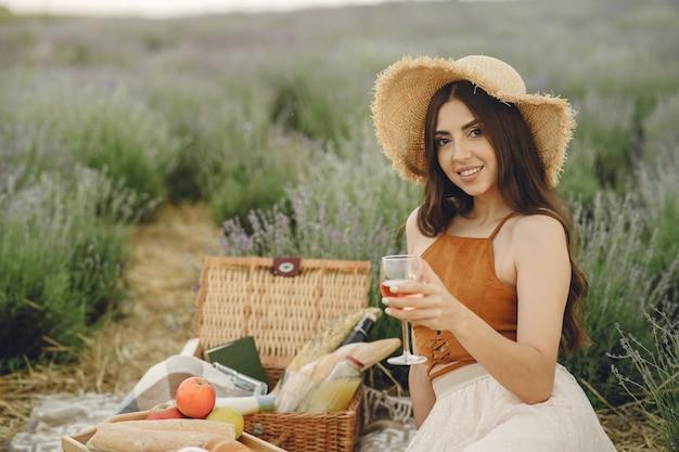 Mulher provençal relaxante no campo de lavanda. senhora em um piquenique. Foto gratuita