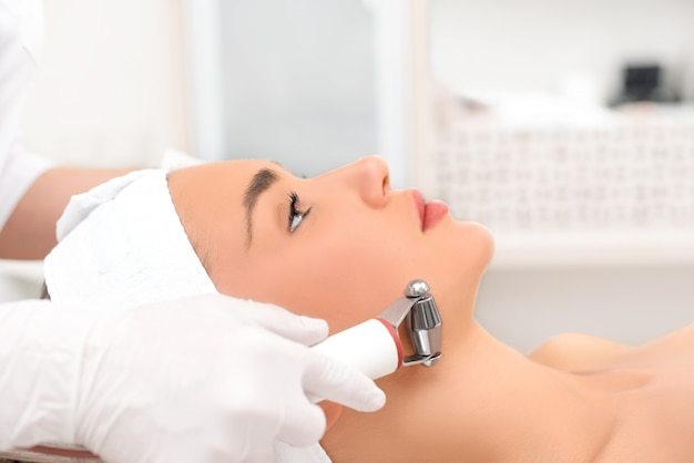 Mulher próxima recebendo massagem facial elétrica no equipamento de microdermoabrasão no salão de beleza. Foto Premium