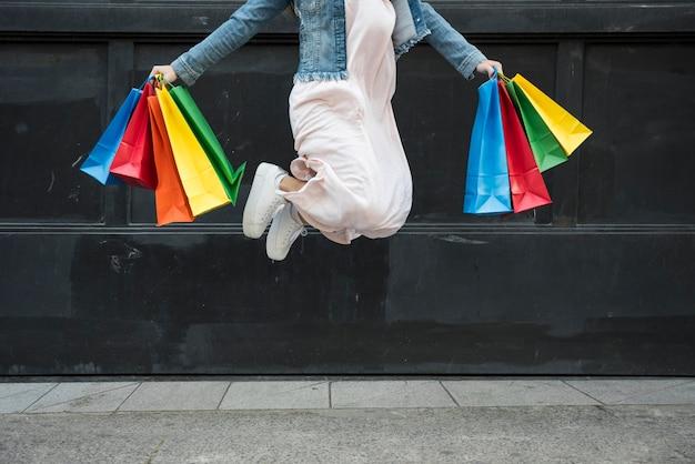 Mulher pulando com pacotes coloridos de compras Foto gratuita