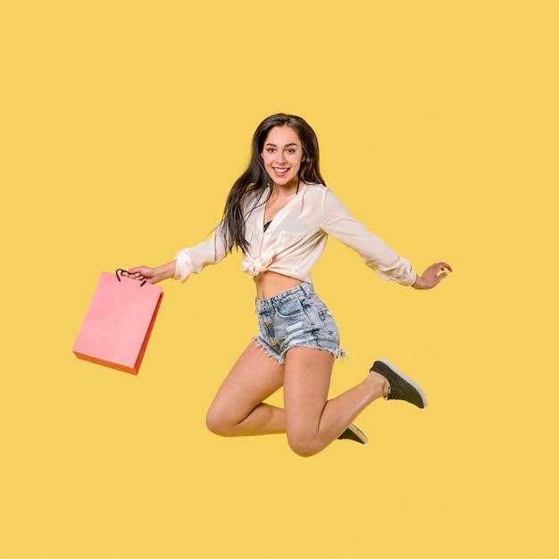 Mulher pulando feliz com saco Foto gratuita