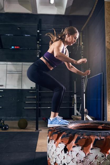 Mulher pulando no pneu no ginásio crossfit Foto Premium