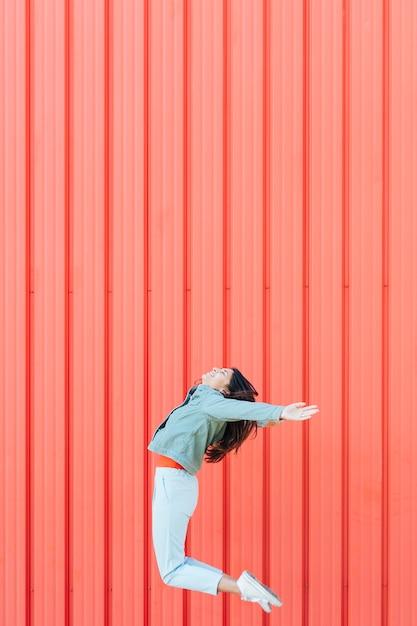 Mulher, pular, ar, contra, vermelho, metal, ondulado, textured, pano de fundo Foto gratuita