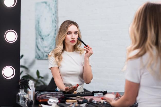 Mulher, pulverizando o rosto com pincel profissional Foto gratuita