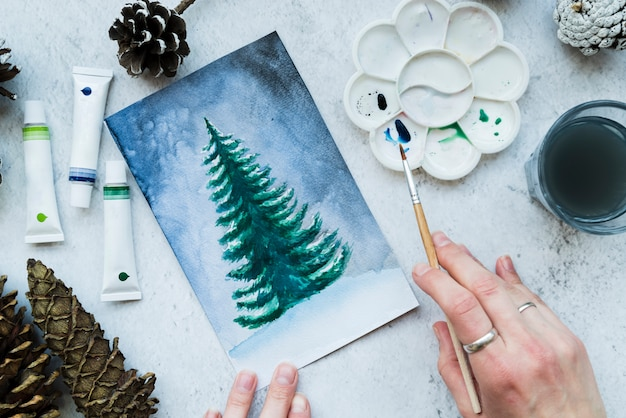 Mulher, quadro, a, árvore natal, com, pintar escova Foto gratuita