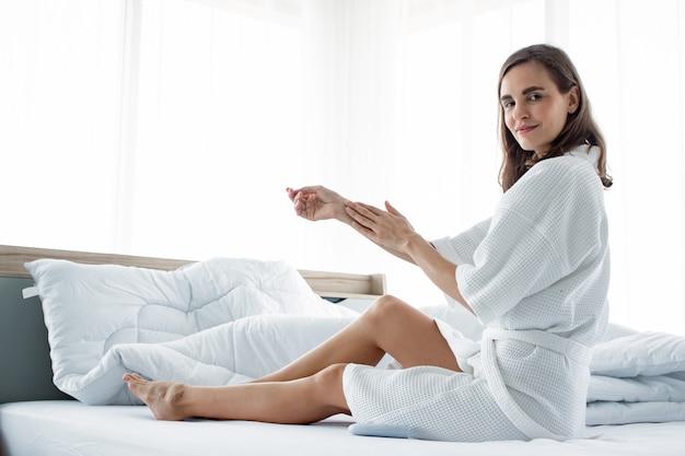 Mulher que aplica o creme de corpo em seu braço na cama branca. Foto Premium