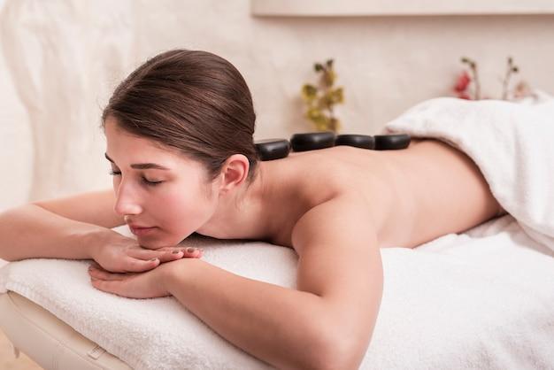 Mulher que aprecia a terapia de rocha no spa Foto gratuita
