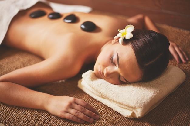 Mulher que aprecia uma massagem com pedras Foto gratuita