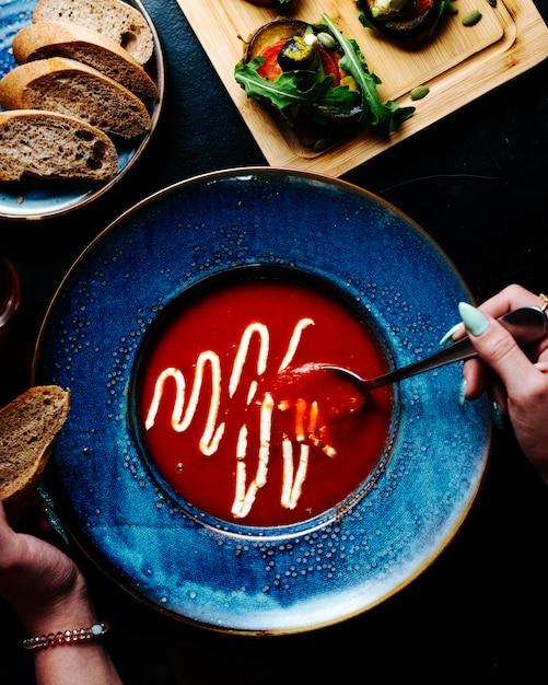 Mulher que come a sopa do tomate com parmesão derretido dentro da placa azul. Foto gratuita