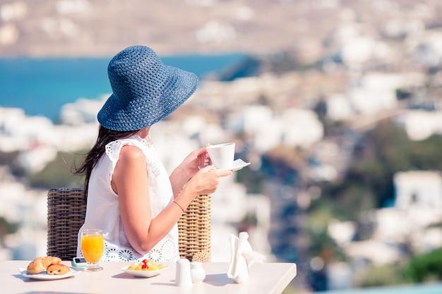Mulher que come o café da manhã no café exterior com vista surpreendente na cidade de mykonos. Foto Premium