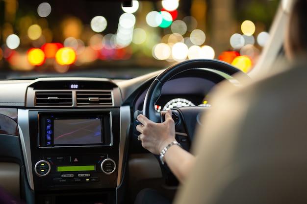 Mulher que conduz um carro com luzes do bokeh do engarrafamento no nighttime. Foto Premium