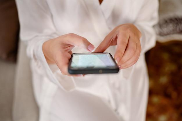 Mulher que consulta seu telefone celular ao esperar em pijamas brancos. Foto Premium