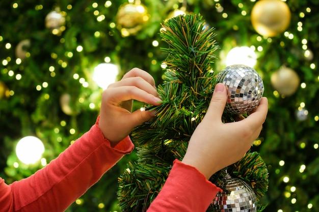 Mulher que decora a árvore de natal no tema da prata e do ouro. Foto Premium