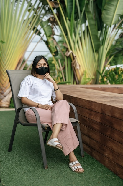 Mulher que desgasta uma máscara protetora que senta-se em uma cadeira ao lado de uma piscina no jardim. Foto gratuita