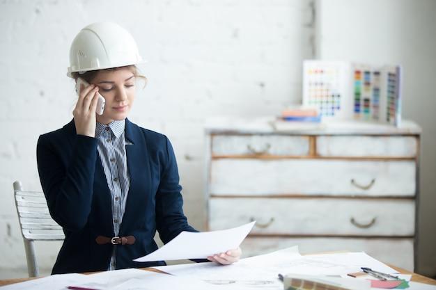 Mulher que fala em um telefone móvel com um capacete Foto gratuita