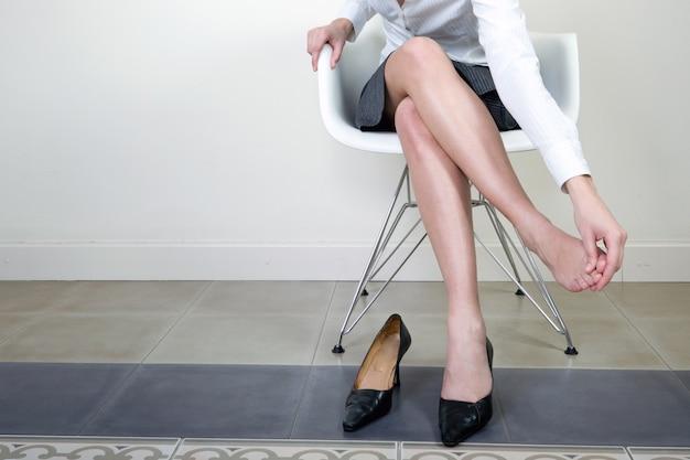 Mulher que faz massagens seus pés após o dia de caminhada Foto gratuita