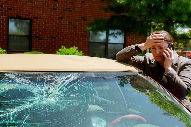 Mulher que faz um telefonema ao lado do carro danificado após um acidente de transito Foto Premium