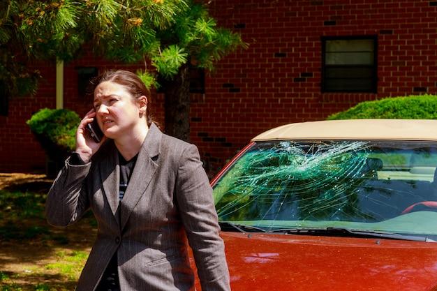Mulher que faz um telefonema pelo pára-brisa danificado após um acidente de transito Foto Premium