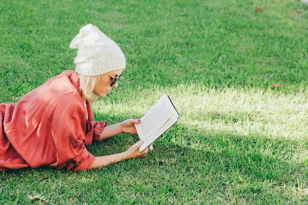 Mulher que gosta de livro na grama Foto gratuita