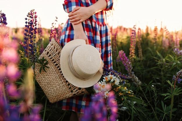 Mulher que guarda o saco e o chapéu da palha, estando no campo de flor no por do sol. Foto gratuita