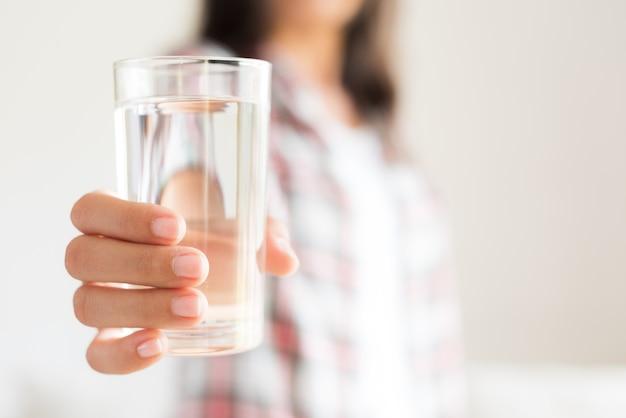 Mulher que guarda o vidro de água potável em sua mão. conceito de cuidados de saúde. Foto Premium
