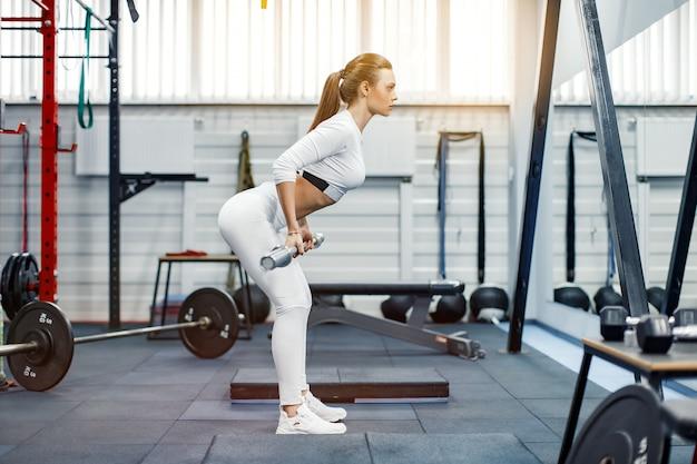 Mulher que levanta um crossfit do peso na ginástica. barra de levantamento terra mulher fitness. Foto Premium