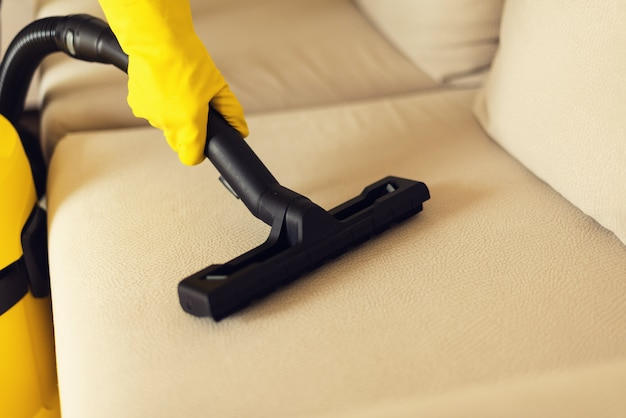 Mulher que limpa o sofá com o aspirador de p30 amarelo. copie o espaço. conceito limpo Foto Premium