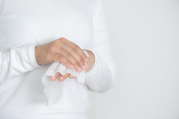 Mulher que limpa suas mãos com tecido molhado ou toalhetes molhados no fundo branco Foto Premium