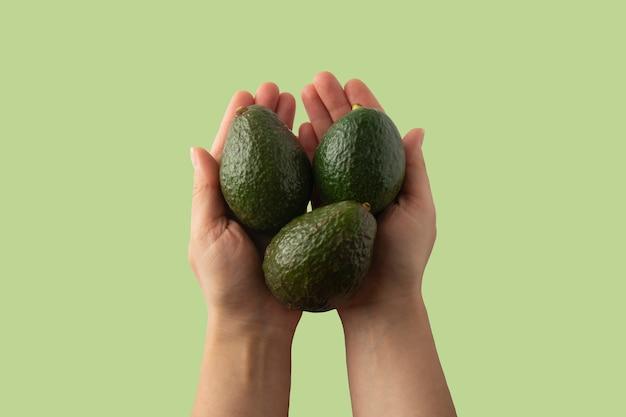 Mulher que mantém o abacate fresco isolado, ascendente próximo. modelo de design. abacate fresco isolado. Foto Premium