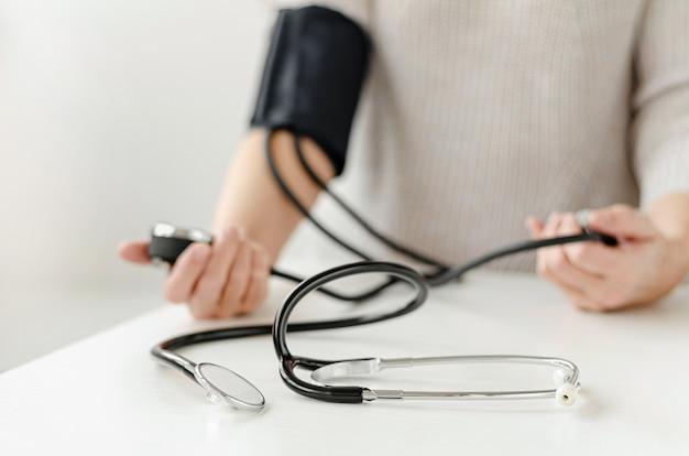 Mulher que mede a pressão sanguínea sozinha em casa com dispositivo manual. auto-cuidado e conceito médico. Foto Premium