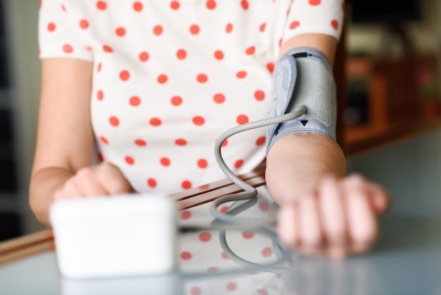 Mulher que mede sua própria pressão sanguínea em casa. Foto Premium