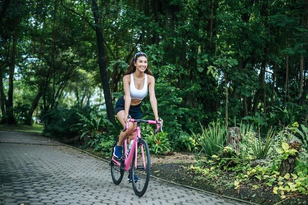 Mulher que monta uma bicicleta da estrada no parque. retrato da mulher bonita nova na bicicleta cor-de-rosa. Foto gratuita